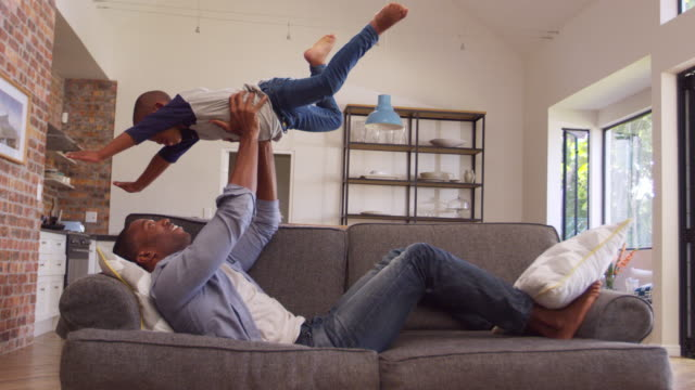 Father And Son Having Fun Playing On Sofa Together Father lifting son in air as they play on sofa together - shot in slow motion living room stock videos & royalty-free footage
