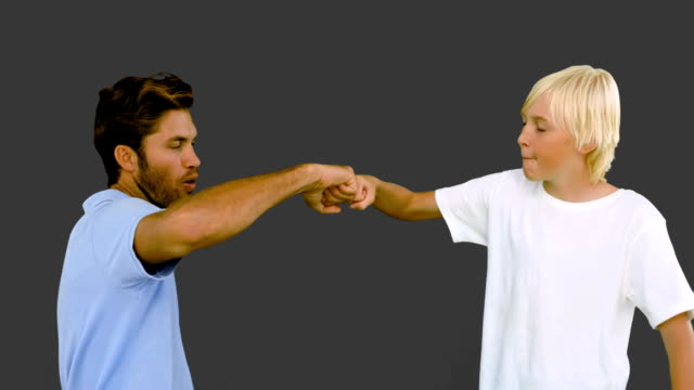 stockvideo's en b-roll-footage met father and son hitting their fists together on grey background - mid volwassen mannen