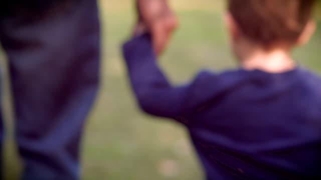 Un Padre e hijo agarrar de la mano mientras unos pasos de distancia - vídeo