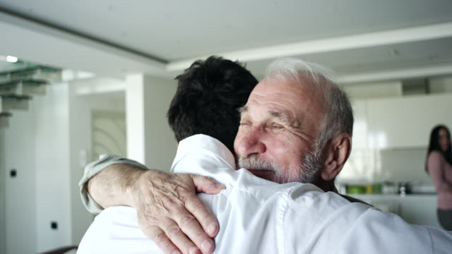 Father and son hugging in living room Senior father and adult son hugging in living room aging process stock videos & royalty-free footage