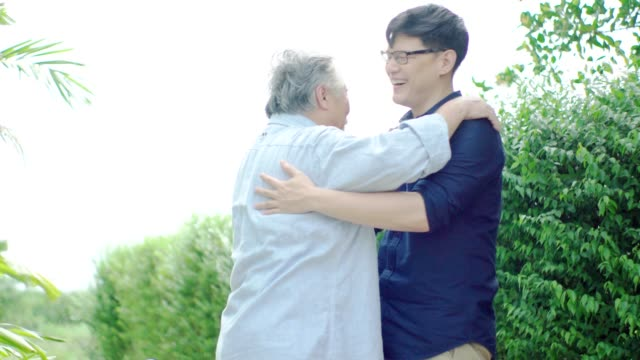 father and son hugging in the garden front of the house. - età miste video stock e b–roll