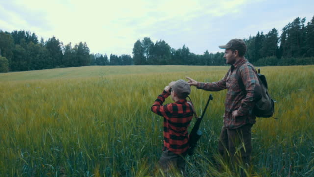 father and son hunting for boar (slow motion) - hunting stock videos and b-roll footage