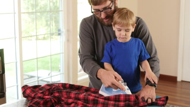 Father and Son ironing shirt together video
