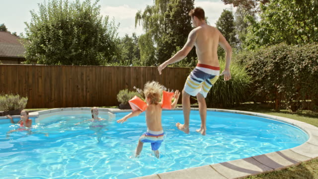 SLO MO CS Father and son jumping into the pool together