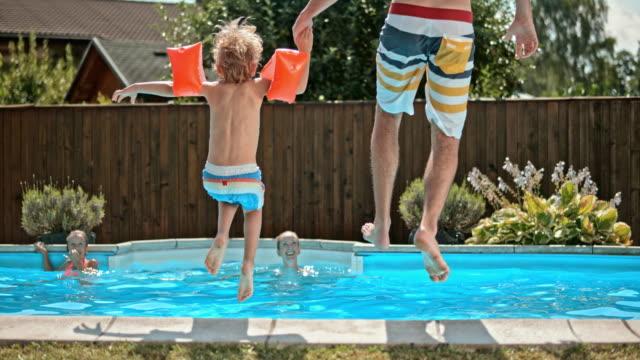 vídeos y material grabado en eventos de stock de cámara lenta ds padre e hijo sumergiéndose en la piscina - jardín privado
