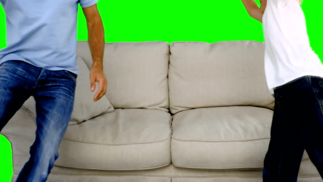 Father and son jumping on the sofa video
