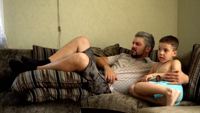 stockvideo's en b-roll-footage met de vader en de zoon liggen samen op de laag en letten tv - ongezond leven