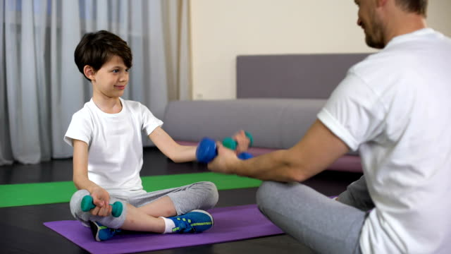 Father and son lifting dumbbells, showing kid fitness exercises, sport family video