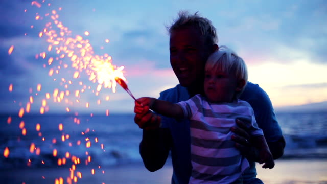 Father and son lighting sparklers on the beach video