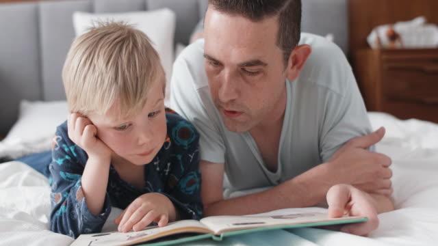 father and son lying in bed reading - jeden rodzic filmów i materiałów b-roll