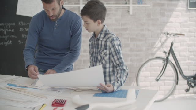 Father and son making a toy plane video