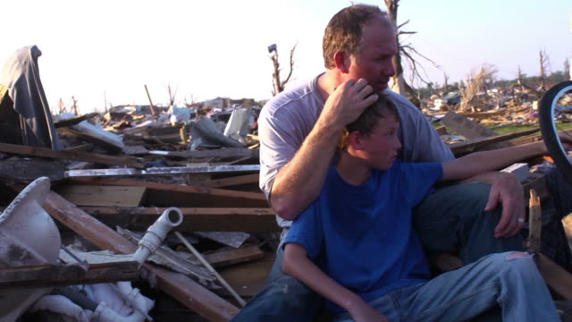 Father and Son - Natural Disaster A father holds his son as he takes in the destruction around him from a natural disaster that has destroyed his town. earthquake stock videos & royalty-free footage