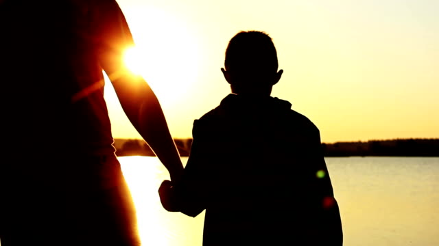 father and son near the river at sunset, silhouettes, father hugs son at sunrise video