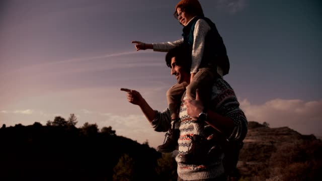 father and son on mountain hiking adventure looking at view - viaggiare zaino in spalla video stock e b–roll