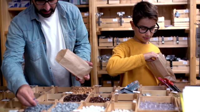 Father and son packed products of plastic in a paper bag video