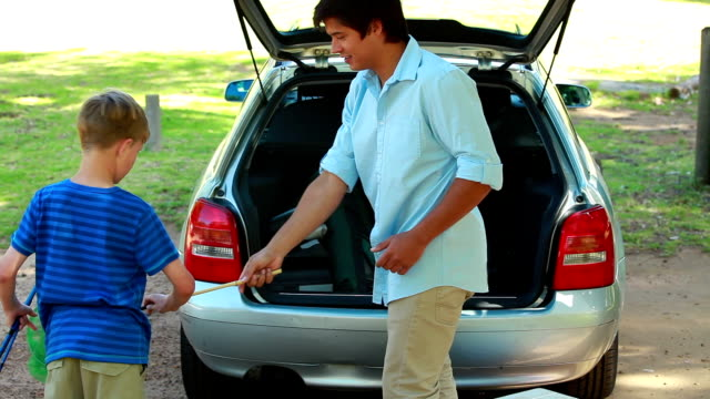 Father and son placing things in the trunk video