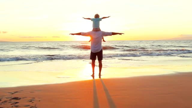 Padre e hijo jugar avión alzar los brazos juntos en la playa al atardecer. - vídeo