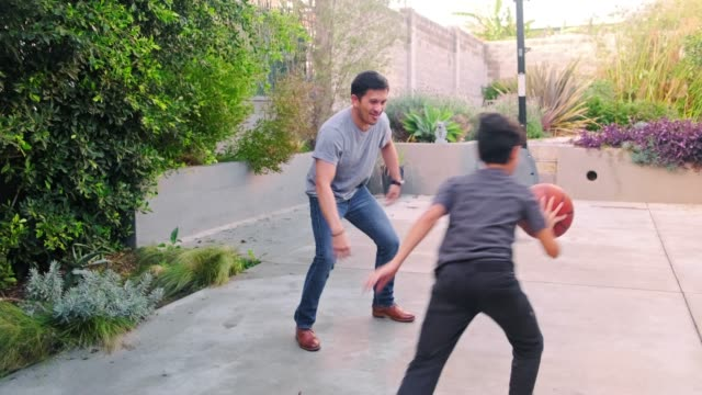 baba ve oğlu arka bahçede basketbol oynuyor - erkek çocuklar stok videoları ve detay görüntü çekimi