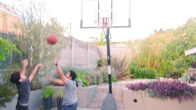 far och son spelar basket på bakgård - basketboll boll bildbanksvideor och videomaterial från bakom kulisserna