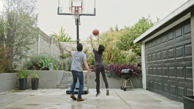 father and son playing basketball in yard - family home video stock e b–roll