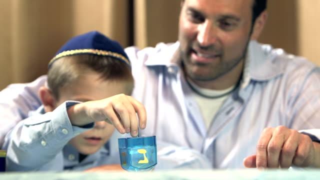 vídeos y material grabado en eventos de stock de padre e hijo jugando trompo - hanukkah