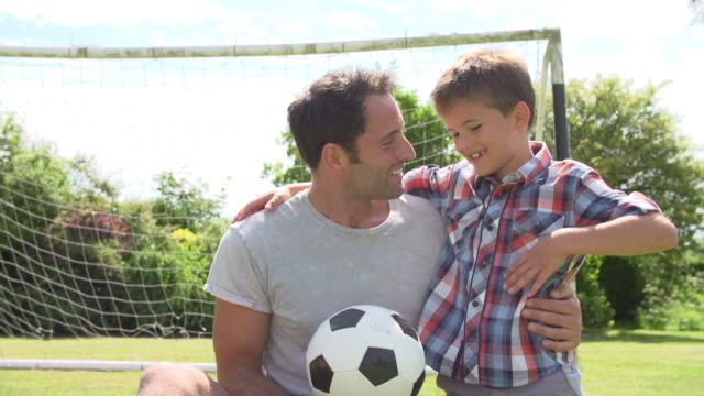 Father And Son Playing Football In Garden At Home video