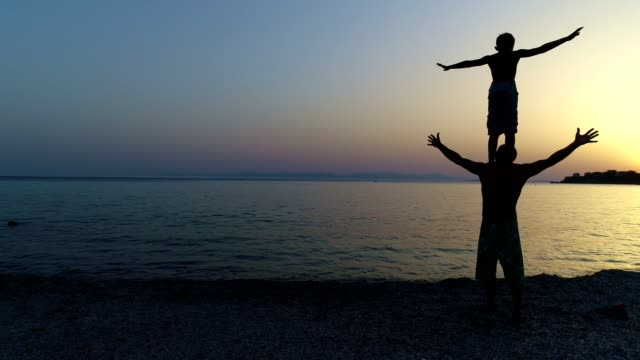 father and son playing on a sunset beach - balance video stock e b–roll