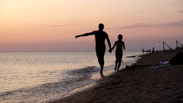 Father and son playing on the beach at the sunset time. Concept of friendly family. video