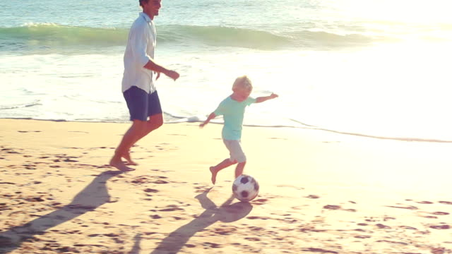 Father and Son Playing Soccer Together at the Beach at Sunset. video