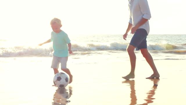 父と息子が一緒にサッカー、夕暮れのビーチです。 ビデオ