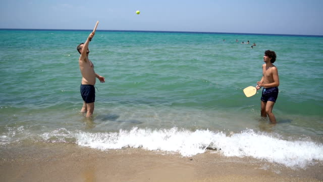Father and son playing tennis on beach
