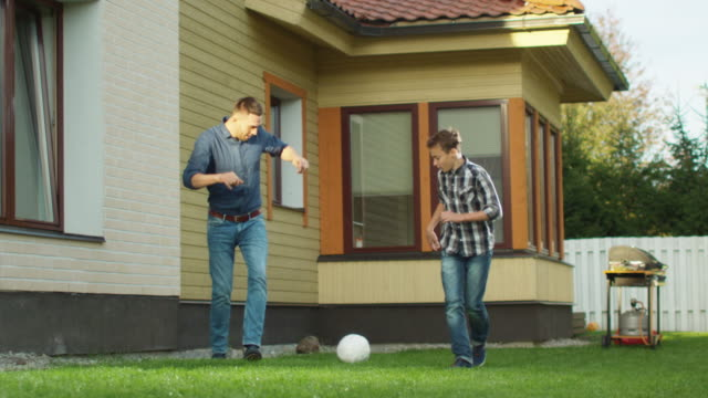 father and son playing with a ball in the backyard. - son stock videos and b-roll footage