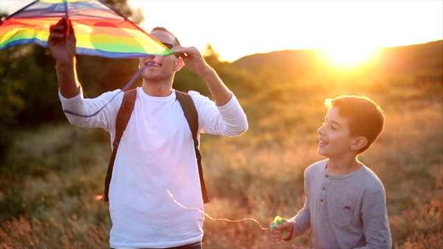 vídeos de stock e filmes b-roll de father and son playing with a kite in nature - homem casual standing sorrir