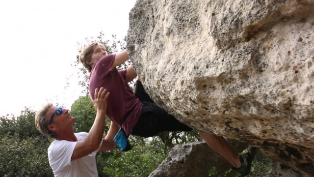 Father and son practice bouldering moves on steep cliff