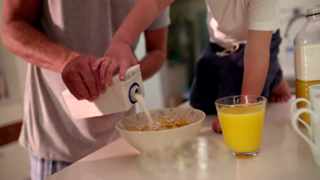 Father and son preparing cornflakes in a bowl with milk video