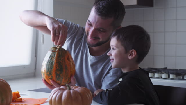 Father and son preparing jack-o-lantern for halloween party