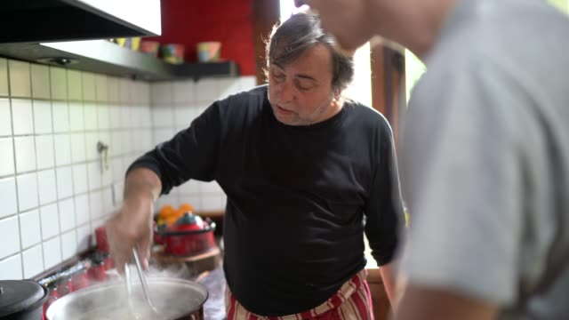Father and son preparing sauce in the kitchen