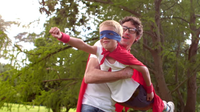 Father and son pretending to be superhero Father and son pretending to be superhero in park cape garment stock videos & royalty-free footage