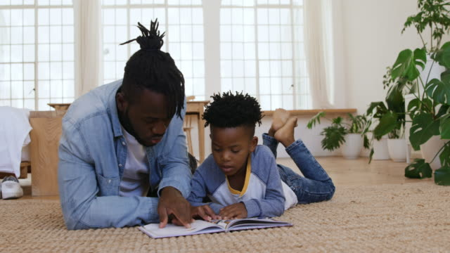 father and son reading a book together at home - tappeto video stock e b–roll
