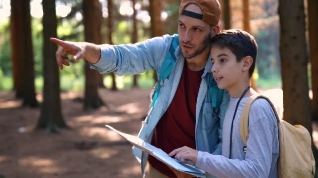 far och son läser karta i skogen - enbarnsfamilj bildbanksvideor och videomaterial från bakom kulisserna