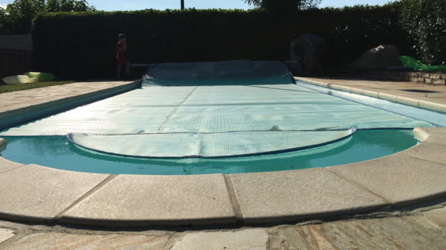 Father and son reel back the thermal cover on a private outdoor swimming pool Filmed in France during a nice long summer holiday covering stock videos & royalty-free footage