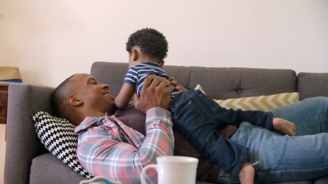 Father And Son Relaxing On Sofa At Home Together video
