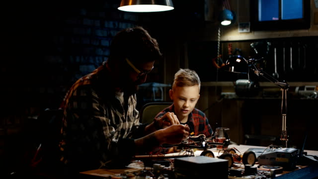 Father and son repairing a drone Medium shot of a father and son repairing a drone with wireless control in a garage hobbies stock videos & royalty-free footage