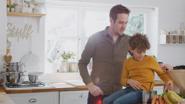 padre e figlio tornano a casa dal viaggio dello shopping usando sacchetti senza plastica che disimballano la spesa in cucina - grocery home video stock e b–roll