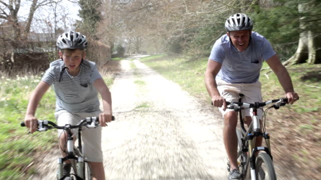 Father And Son Riding Bikes Along Country Track video