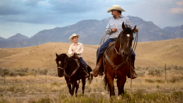 Father and son riding horses Father and son riding horses in western America ranch. wild west stock videos & royalty-free footage