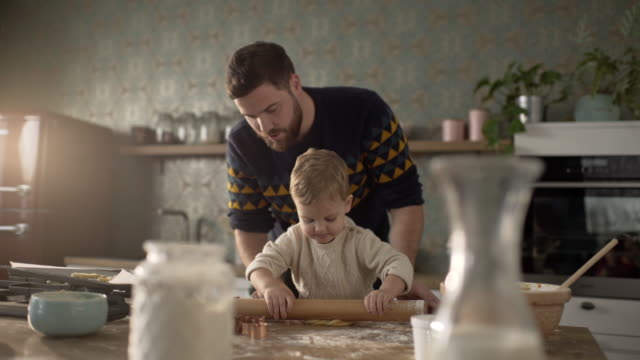 Father and son rolling dough in the kitchen