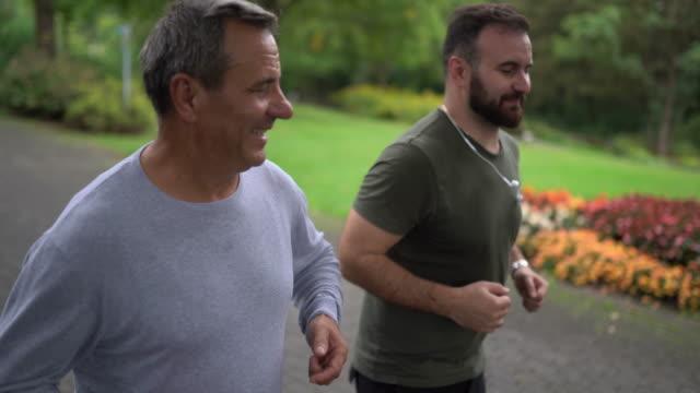 ojciec i syn biegają rano w naturze - syn filmów i materiałów b-roll