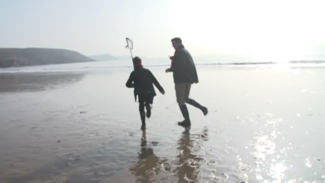 父と息子のビーチでのランニングで、冬の漁網 - 釣りをする点の映像素材/bロール