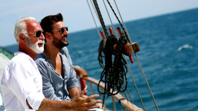 vídeos de stock e filmes b-roll de father and son sailing. - enjoying wealthy life